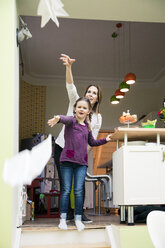 Happy mother and daughter throwing paper plane together at home - MOEF01096