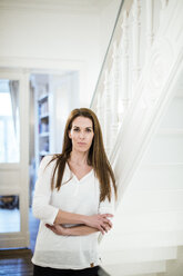 Portrait of woman at home leaning against staircase - MOEF01099