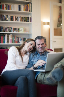 Happy couple sitting on couch using laptop - MOEF01108