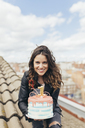 Portrait of woman presenting Birthday cake on roof - JPF00307