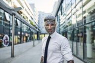 Young businessman with tattooed face walking in the city, portrait - ZEDF01329