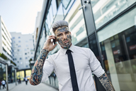 Young businessman with tattooed face, talking on he phone - ZEDF01332