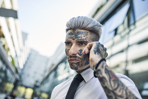 Young businessman with tattooed face, talking on he phone - ZEDF01335