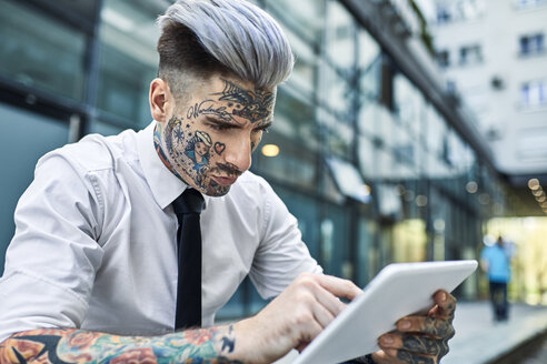 Young businessman with tattooed face, using digital tablet - ZEDF01344