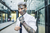 Young businessman with tattooed face, fastening tie - ZEDF01347