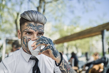 Young businessman with tattooed face, drinking coffee - ZEDF01350