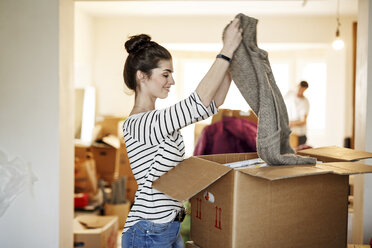 Young woman moving house, unpacking cardboard boxes - PESF01086