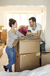 Young couple moving house, unpacking cardboard boxes - PESF01089