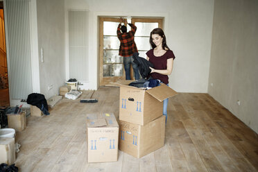 Couple moving into their new home, woman unpacking boxes - PESF01092