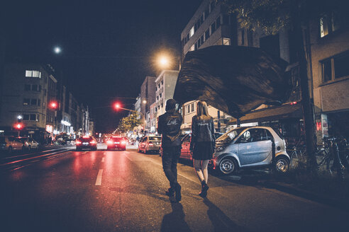 Back view of young couple with black flag walking on the street by night - GUSF00719