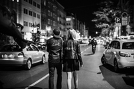Back view of young couple with black flag walking on the street by night - GUSF00722