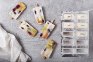 Homemade fruits and yogurt ice lollies on marble - RTBF01209