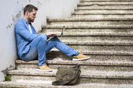 Young man sitting on stairs, working, using laptop - JSMF00145