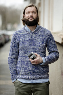Man with beard standing in street, holding old camera - FLLF00003