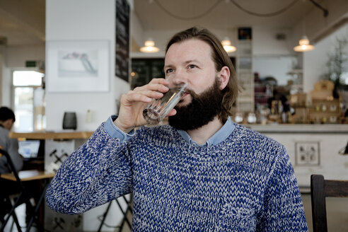 Man with beard sitting in cafe, drinking water - FLLF00006