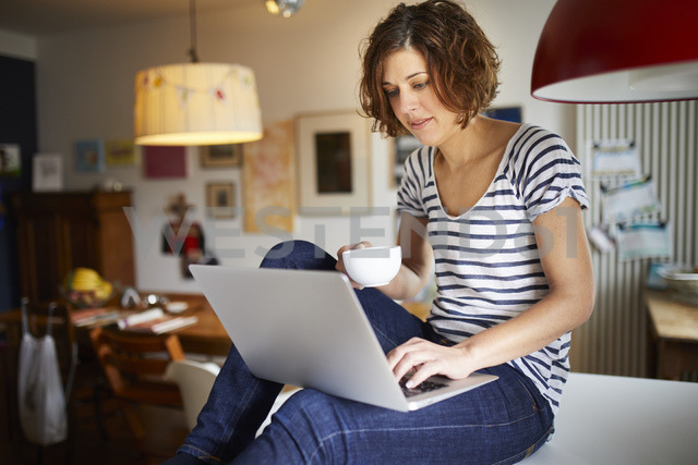 Portrait of mature woman sitting on kitchen table using laptop - PNEF00621
