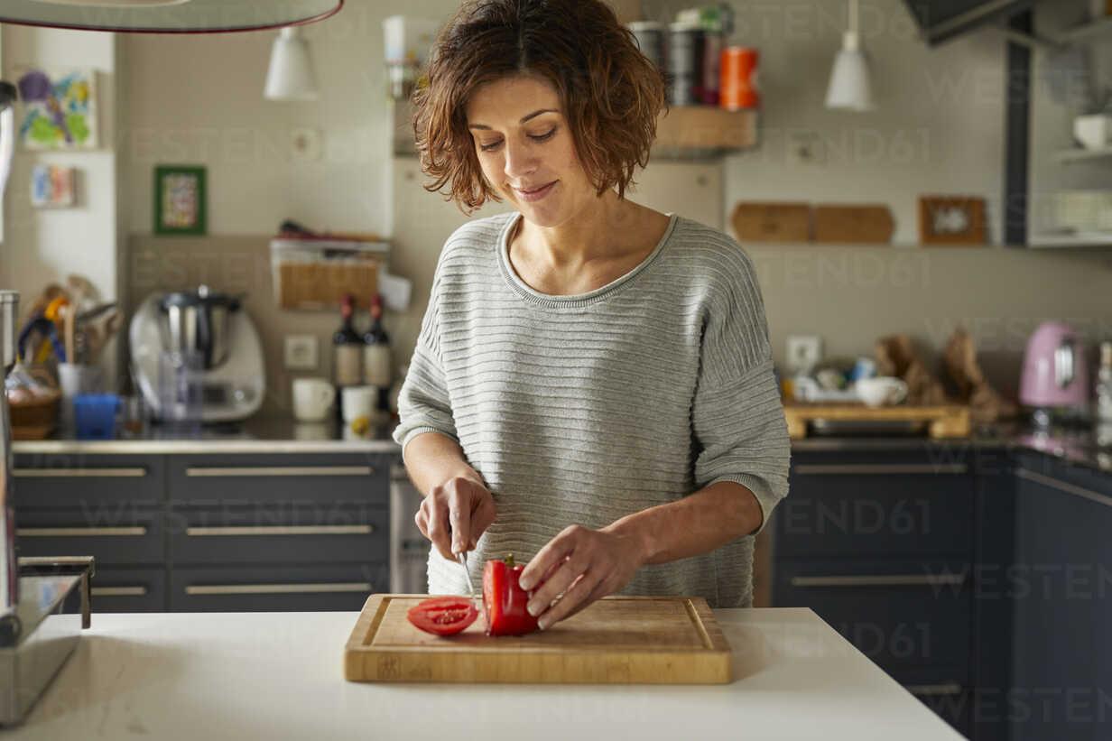 Reife Frau schneidet Tomate in der Küche - Stockfoto