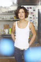 Portrait of mature woman wearing white tank top standing in the kitchen - PNEF00636
