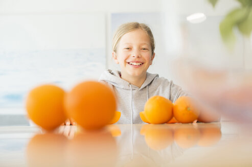 Portrait of happy girl with oranges in kitchen - NEKF00030