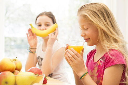 Portrait of girl drinking glass of orange juice while her friend having fun with banana - NEKF00036