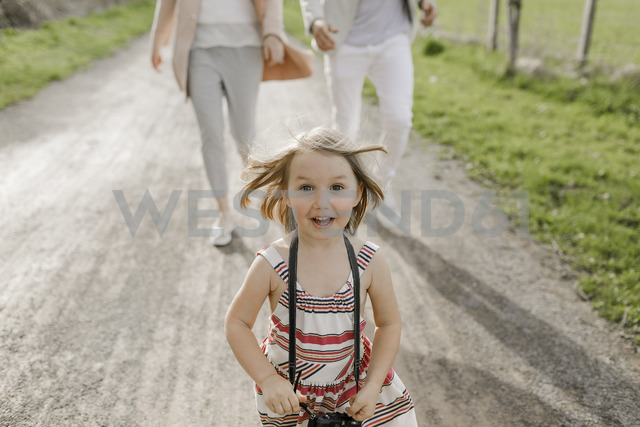 Portrait of excited little girl with camera - KMKF00235
