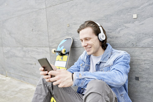Young man with skateboard sitting on ground, using digital tablet - FMOF00366
