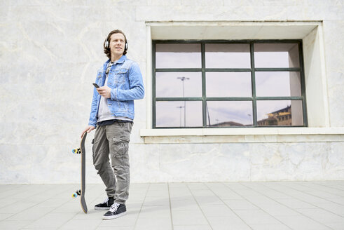Young man holding skateboard, using smartphone - FMOF00372