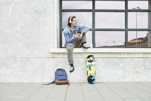 Young man sitting on window sill, waiting, using smartphone - FMOF00375