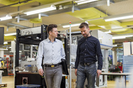 Two men talking in factory - DIGF03976
