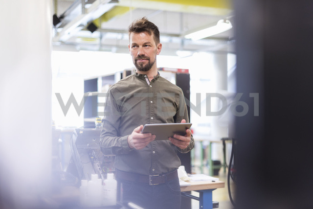 Smiling man standing in factory with tablet looking sideways - DIGF04012 - Daniel Ingold/Westend61