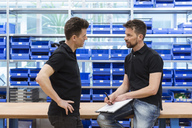 Two men talking in factory storeroom - DIGF04018