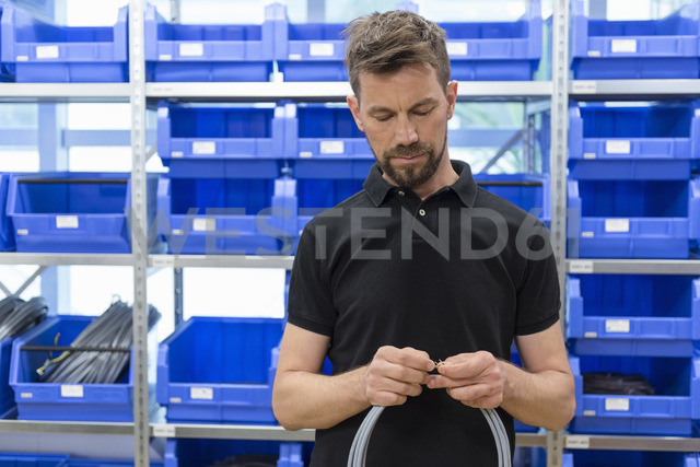 Man holding cable in factory storeroom - DIGF04021