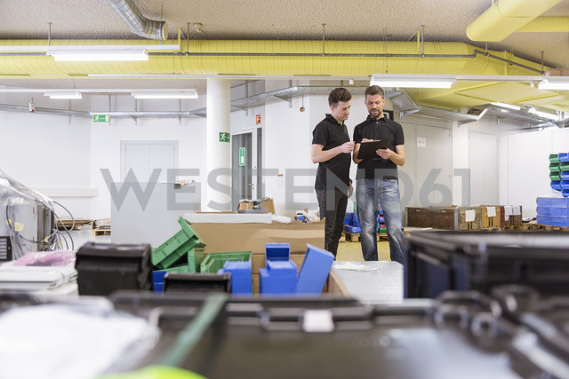 Two men with clipboard talking in factory - DIGF04024