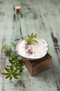 Glass bottle of woodruff sirup and bowl of natural yoghurt with chia and woodruff sirup - MYF02030