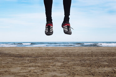 Legs of man jumping in the air on the beach - RTBF01222