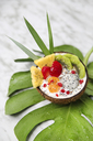 Coconut bowl with variuos fruits, natural yoghurt and seeds on leaf - RTBF01225