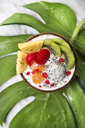 Coconut bowl with variuos fruits, natural yoghurt and seeds on leaf - RTBF01228