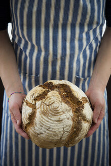 Woman holding homemade sourgough rye bread - LVF06908