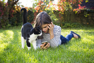 Girl with smartphone and cat on a meadow - LVF06913