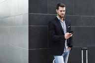 Young businessman looking at his smartphone - JSMF00151