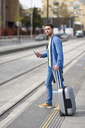 Young man waiting at a station with smartphone in his hand and trolley - JSMF00154