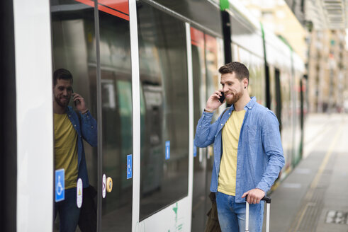 Young man with smartphone in front of tram - JSMF00160
