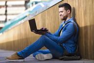Young man sitting on footbridge using laptop - JSMF00166