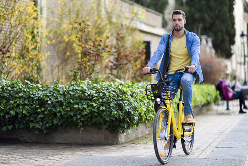 Young man riding rental bike in the city - JSMF00172