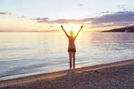 Greece, Pelion, Pagasetic Gulf, woman on the beach with raised arms at sunset, Kalamos in the background - MAMF00081