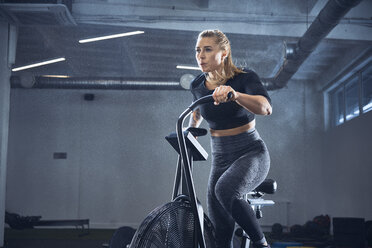 Athletic woman doing airbike workout at gym - BSZF00306