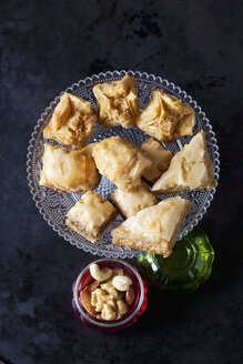 Baklava on cake stand and bowl of nuts on dark ground - CSF29107