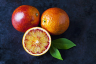 Two whole and a half blood orange on dark ground - CSF29110