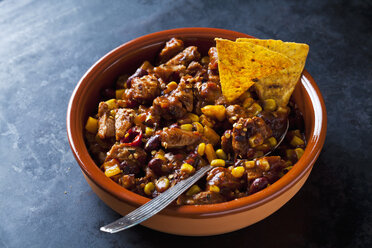 Vegetarian Chili with soy meat cut into strips and tortilla chips in earthenware dish - CSF29116