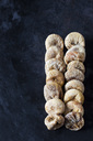 Two rows of dried figs on dark ground - CSF29146